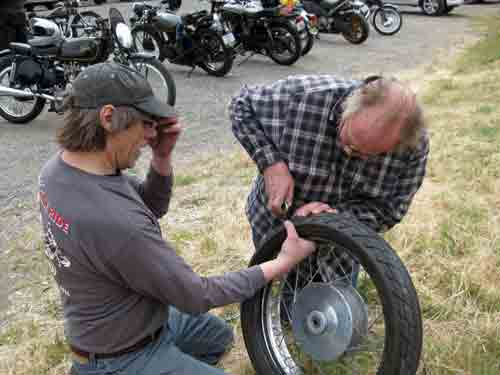 Mork pulls the screw out of the tire.