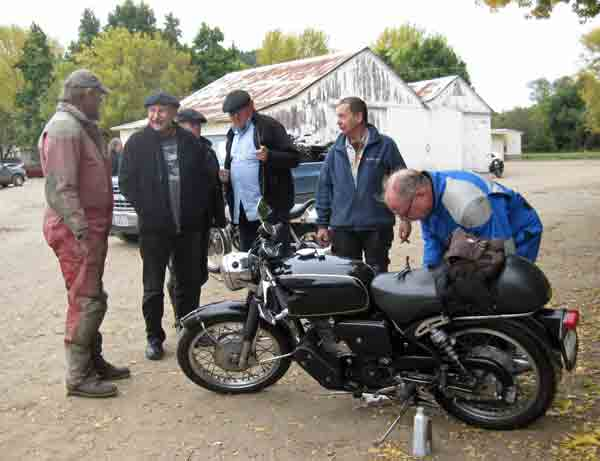 While Fred pours oil in the bike, others give George advice